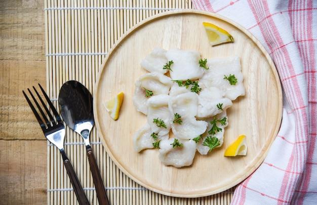 レモンとスパイスのダイニングテーブルの上の木製トレイに日本料理の魚の切り身