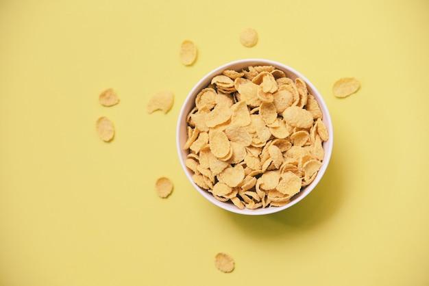 コーンフレークのシリアル健康的な食品のための黄色の背景にボウルに朝食