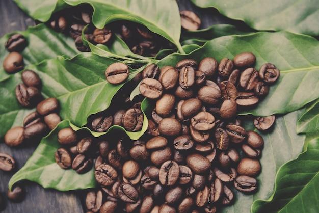 Кофе в зернах на листе - жареный кофе на темном деревянном столе