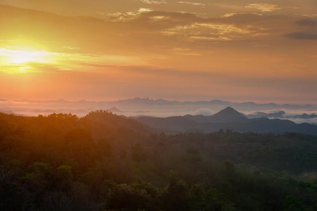 朝の霧の霧の丘の上の美しい空日の出アジア風景