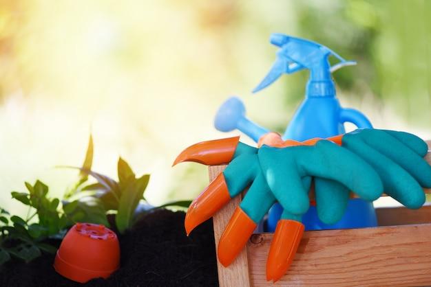 機器園芸用手袋ゴムじょうろ、植栽植物と土の上の木と木箱の園芸工具