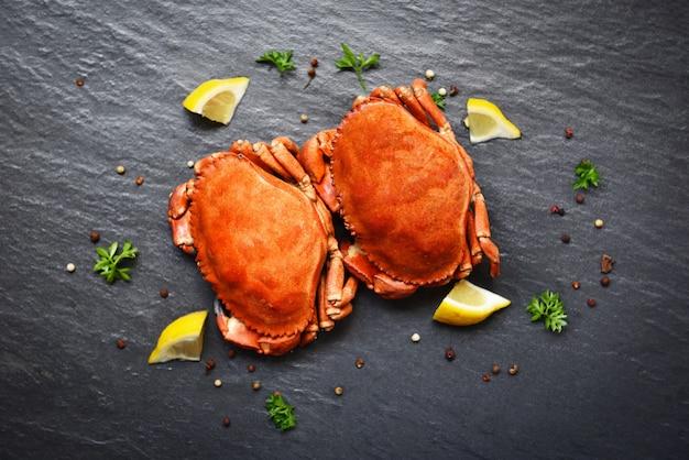 Крабы, приготовленные с лимоном на тарелке, подаются на темной тарелке - морепродукты на каменном крабе, приготовленные на пару