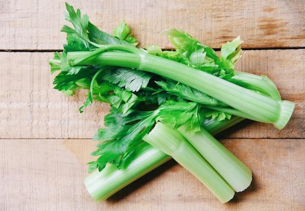 セロリの棒と新鮮な野菜の葉、木の上のセロリの茎の束