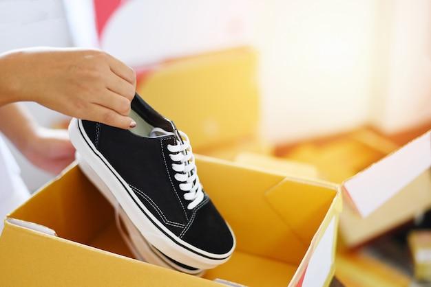 Продажа интернет-магазинов - женщина упаковывает кроссовки в картонную коробку, готовит посылочную коробку к службе доставки, клиент, электронная коммерция, доставка, покупки онлайн и концепция заказа.