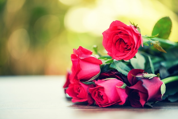 赤いバラの花の花束/木製のテーブルの自然にピンクと赤のバラのバレンタインデーの愛