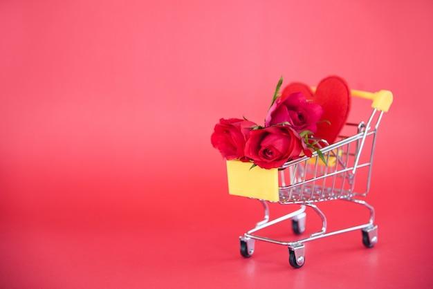 バレンタインデーの買い物とバラの花赤いハートがいっぱい入ったショッピングカートとバレンタインデーのバラ