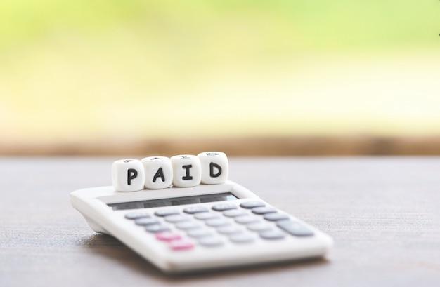 支払われた言葉とオフィスビジネスで時間支払われた支払いのためのテーブルの上の電卓