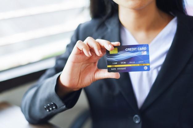 オフィスでのオンラインショッピングのためのクレジットカードを持っている女性の手/テクノロジーマネー財布オンライン支払いを支払っている働く人々