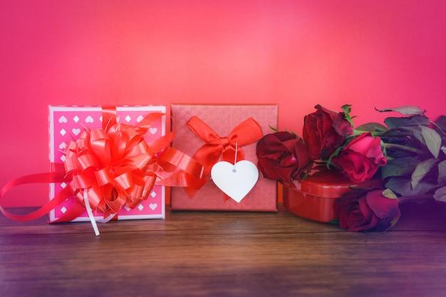 Подарочная коробка на день святого валентина, красная и розовая на дереве. день святого валентина, красная роза.