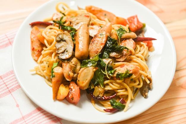 Горячий и пряный спагетти-паста с помидорами, чили и базиликом, вид сверху - традиционная вкусная итальянская еда спагетти с колбасой на тарелке на обеденном столе
