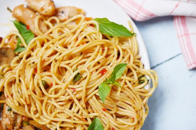Макароны спагетти и томатный перец чили и овощи с листьями базилика - традиционная вкусная итальянская еда спагетти болоньез на тарелке на обеденном столе