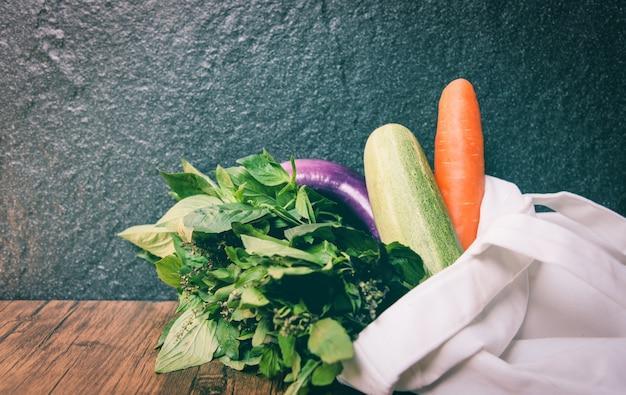 ゼロの無駄はより少ないプラスチック概念/市場の自由なプラスチック買物をすることからの木のテーブルの白いトートキャンバスの布袋のエコ綿生地袋で有機性新鮮な野菜