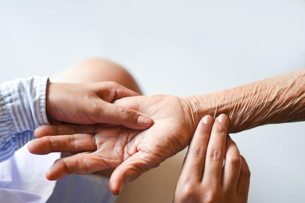 Старший пациент и медсестра измерение пульса вручную