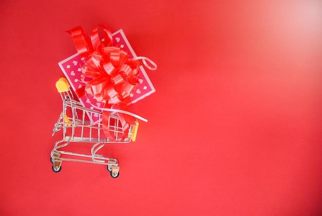 バレンタインの日のショッピング、ギフトボックスピンクのプレゼントボックスショッピングカートのコンセプトに赤いリボンの弓