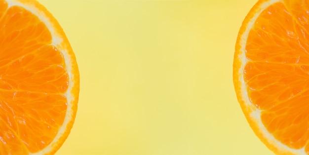 Долька апельсина на желтом фоне. крупным планом свежих оранжевых фруктов, вид сверху макро фруктов