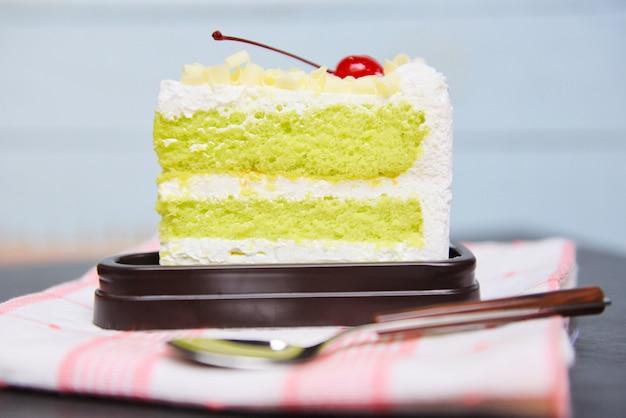 チェリーフルーツとテーブルの上の白い皿にクリームと緑のケーキのスライス。おいしい緑茶チーズケーキ