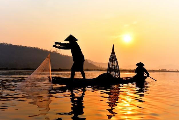 メコン川のネット日没または日の出を鋳造木製ボートに使用してアジア漁師ネット