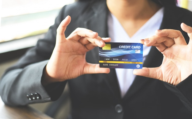オフィスでのオンラインショッピングのためのクレジットカードを保持している女性手