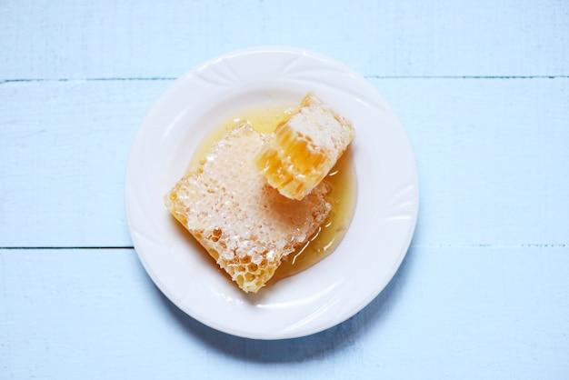 白いプレートの自然な健康食品に黄色の甘いハニカムスライスのクローズアップ