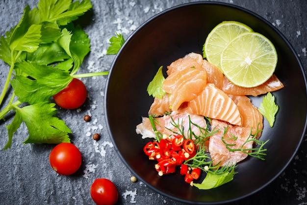 サーモンサラダ魚のサケの切り身の塊と暗い背景に生のサーモン刺身シーフードのレモンハーブとスパイスのクローズアップ
