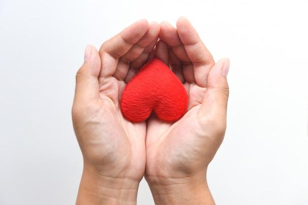 慈善事業コンセプトの手に心。バレンタインの日のための手で赤いハートを保持している女性や愛の暖かさを与える助けを寄付