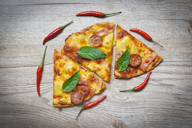 木製トレイとチリバジルの葉の上面のピザ。おいしいおいしいファーストフードイタリアの伝統的なピザチーズとモッツァレラチーズ。