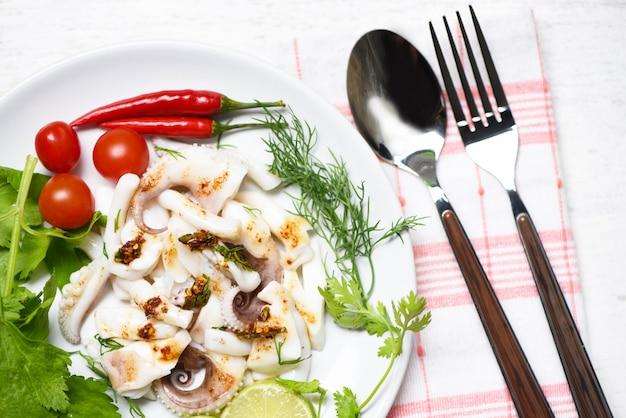 レモンハーブとダイニングテーブルの上面にスパイスのイカのサラダ。タコ料理の前菜料理辛くて辛いチリソース。