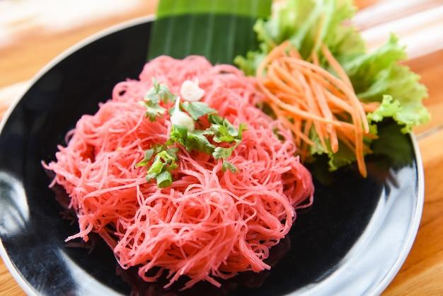 米春雨のピンクのフライパンと野菜の炒めた赤米炒め麺は、木製のテーブルのプレートで提供していますタイ風アジアンヌードル
