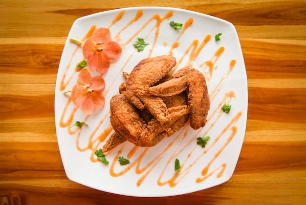 揚げ手羽先のソースを添えたプレートで提供しています。木製のテーブルにシャキッとした鶏手羽肉のプレート。