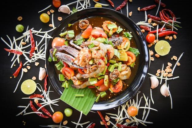 新鮮なエビのカニ貝のスパイシーなシーフードサラダは、黒プレートの新鮮な野菜のハーブとスパイスの材料で提供されます。