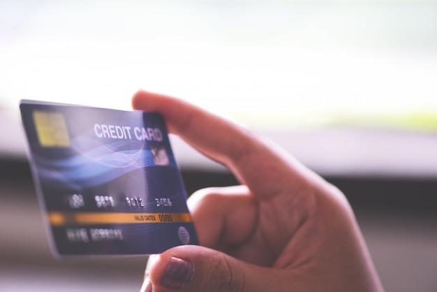 女性の手が自宅でオンラインショッピングのクレジットカードを保持しています。テクノロジーマネーウォレットオンライン支払いを支払う人々。