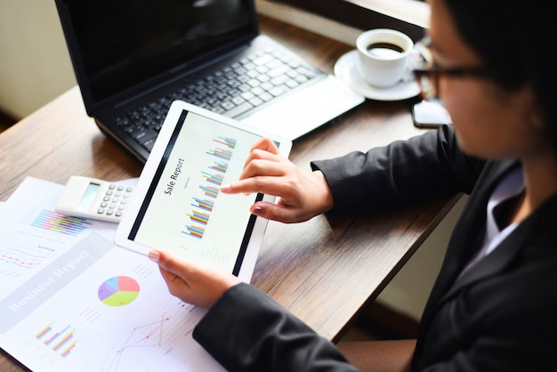 電卓とタブレットコンピューター技術のラップトップを使用してビジネスレポートをチェックしてオフィスで働くビジネスウーマン。