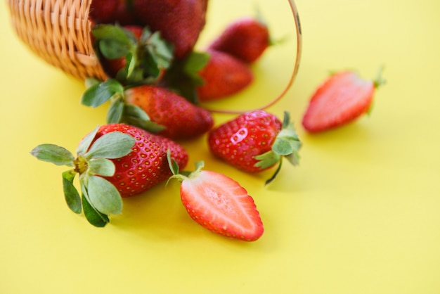 黄色の背景に新鮮なイチゴ。バスケットで熟した赤いイチゴ狩り