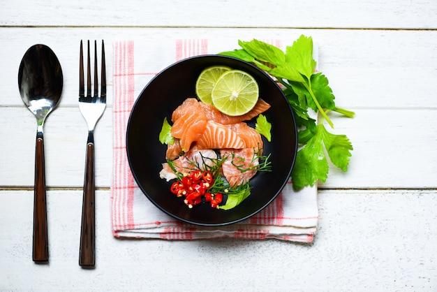 魚のサケの切り身のボーリングとダイニングテーブルの背景にスプーンフォーク