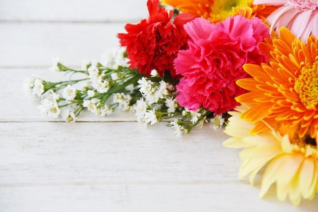 Свежие весенние летние цветы обрамляют композицию тропического растения герберы