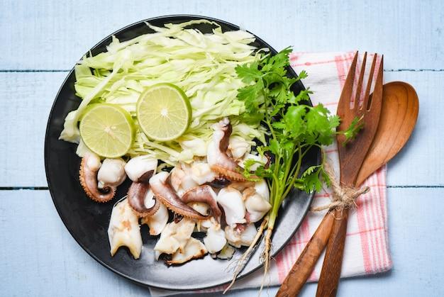 イカのグリルサラダ、ライムハーブとスパイスのダイニングテーブル、触手のタコ料理の前菜料理ホットでスパイシーなシーフード料理