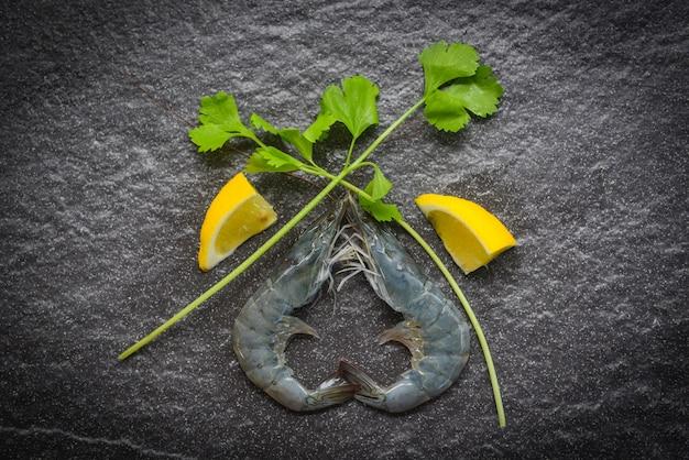 暗い皿に生えびシーフードレストランで暗い背景にスパイスレモンとセロリと新鮮なエビ