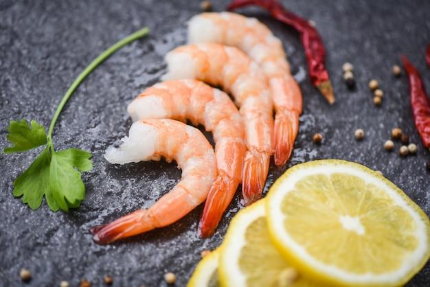 シーフードレストランでスパイスとレモンで調理した皮をむいたエビ海老の暗いプレートで提供される新鮮なエビ