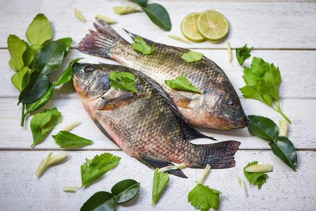 アジアのレストランで食べ物を調理するためのティラピア魚淡水とレモンライムハーブ野菜木製の背景に新鮮な生ティラピア