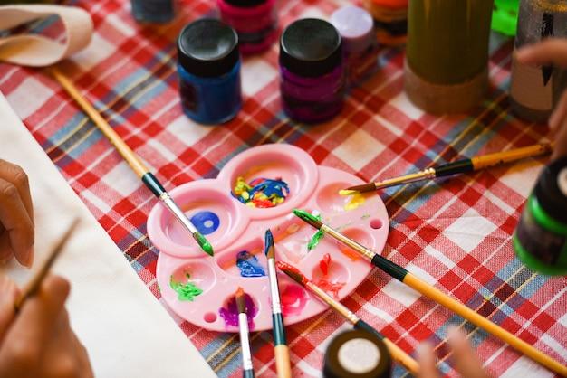 テーブルのペイントブラシパレットと水彩絵の具