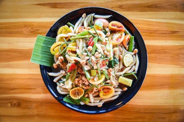 Салат из папайи с овощной лапшой и арахисом подается на стол с рисовой лапшой и пряными блюдами тайской кухни