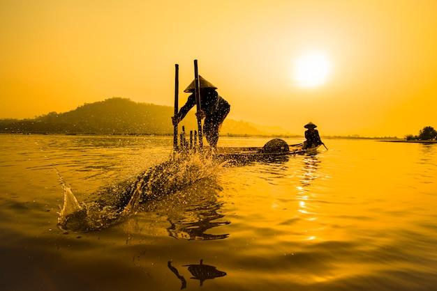 ボート川の夕日の漁師ボート夕日または日の出のアジア漁師竹魚トラップ