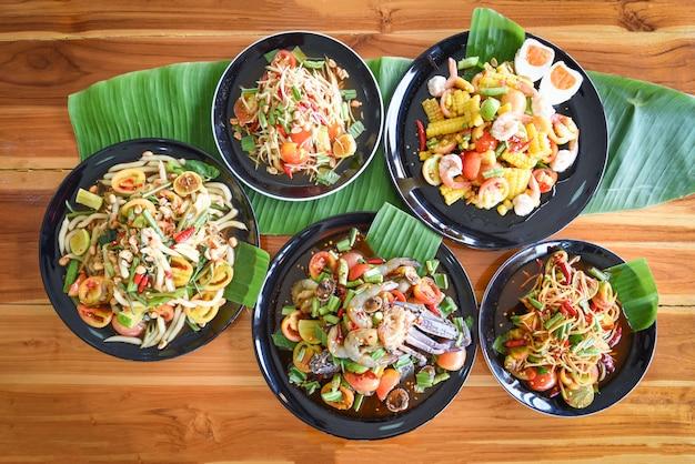 パパイヤサラダダイニングテーブルで提供しています緑のパパイヤサラダ新鮮な野菜の皿にスパイシーなタイ料理
