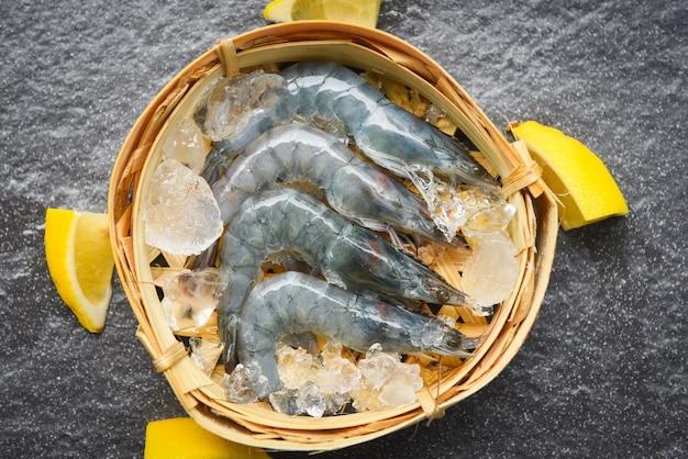 竹の蒸し器で生えび、アイススパイス、暗いプレートのレモン、レストランで新鮮なエビ
