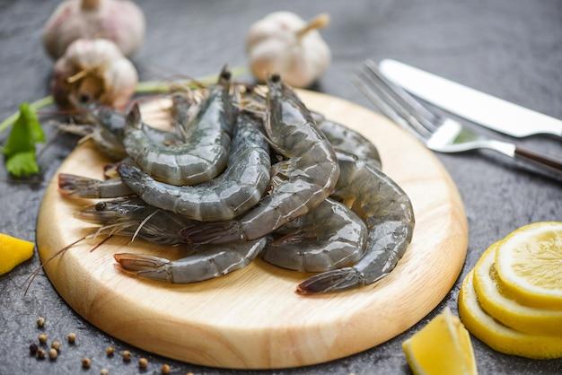 木製のまな板の上の生えびスパイスレモンで調理するための新鮮なエビエビ