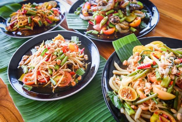 Салат из папайи, подается на обеденном столе салат из зеленой папайи, острая тайская еда на тарелке