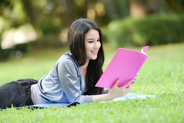 アジアの女性は屋外の本を読むガーデンパーク