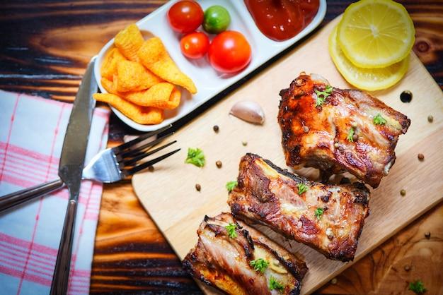 テーブルで提供されるトマトケチャップとハーブスパイスで焼いたバーベキューポークリブ