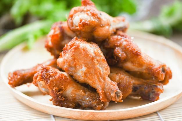 Жареные куриные крылышки на деревянной тарелке