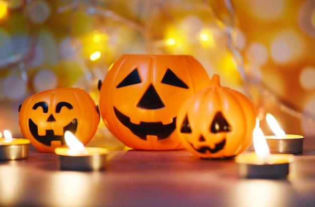 Хэллоуин при свечах оранжевого цвета, украшенные праздниками, праздничная концепция - смешные рожи джека о, фонарь, тыква, хэллоуин украшения для вечеринки